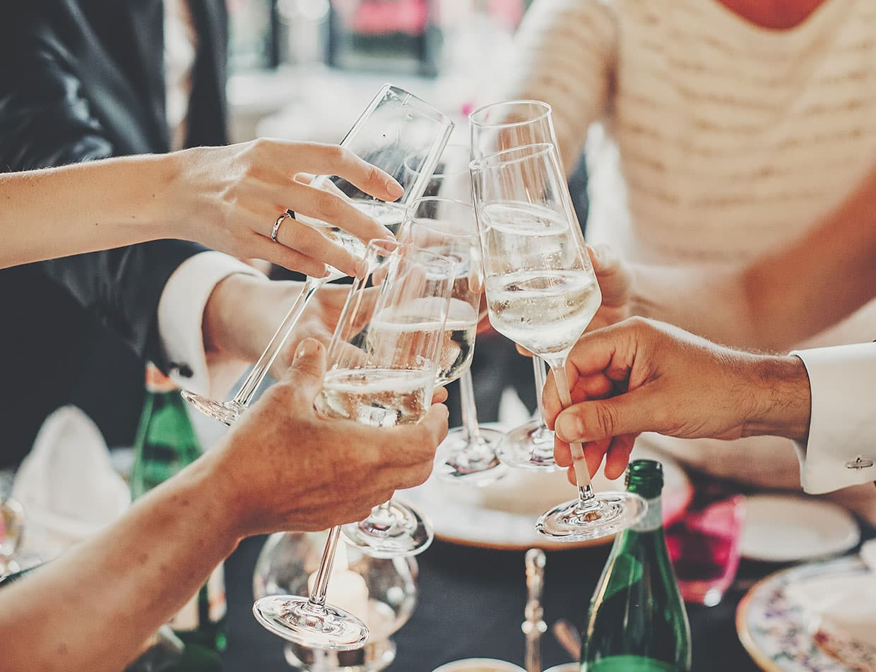 Couple toasting champagne with wedding guests